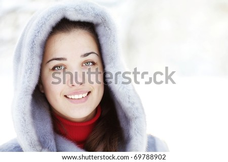Portrait of a happy young woman in fur coat outdoors - stock photo