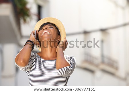 Portrait of a happy young woman laughing with cell phone - stock photo