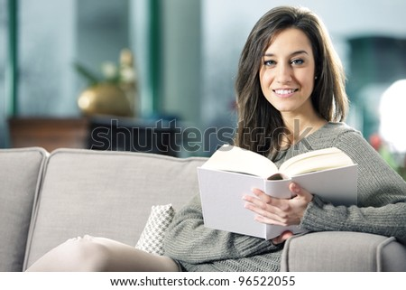 Portrait of a happy young woman lying on couch with book - stock photo