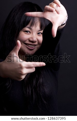 Portrait of a happy young woman making a snapshot sign - stock photo