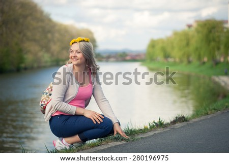 Portrait of a happy young woman outdoors on a weekend excursion - stock photo
