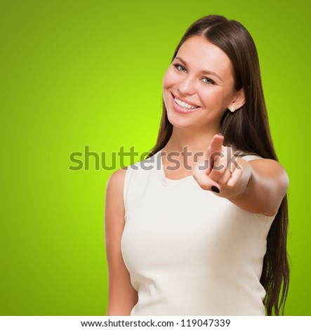 Portrait Of A Happy Young Woman Pointing At You against a green background - stock photo
