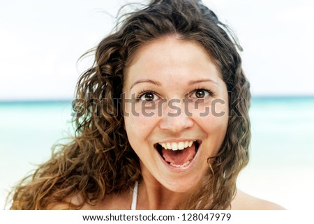 Portrait of a happy young woman posing while on the beach - stock photo