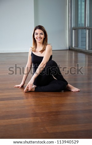 Portrait of a happy young woman practicing yoga called Half Spinal Twist on wooden floor - stock photo