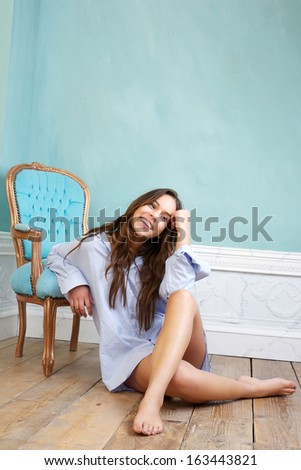Portrait of a happy young woman sitting on wood floor and relaxing at home