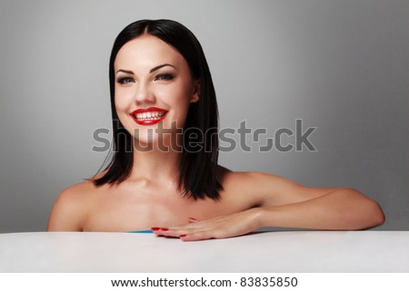 Portrait of a happy young woman smiling against grey background - stock photo
