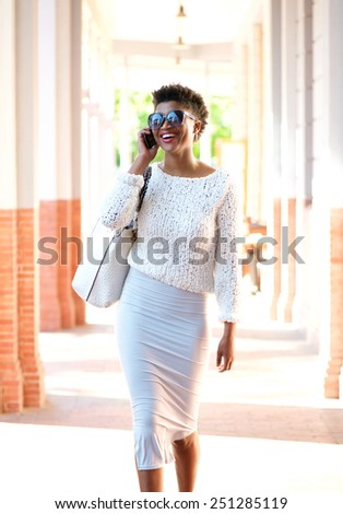 Portrait of a happy young woman walking and talking on mobile phone - stock photo