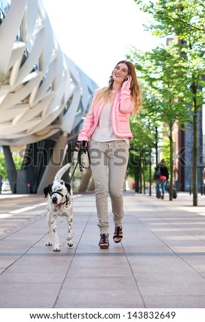 Portrait of a happy young woman walking her dog and talking on cellphone in the city - stock photo