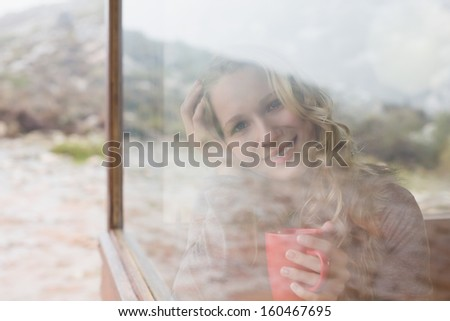 Portrait of a happy young woman with coffee cup looking out through cabin window