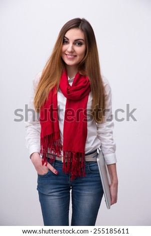 Portrait of a happy young woman with laptop over gray background - stock photo