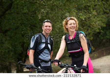 Portrait of a healthy couple smiling with bicycles  - stock photo