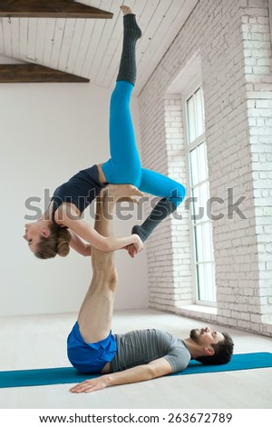 Portrait of a healthy girl and guy doing exercise to relax in the gym. yoga