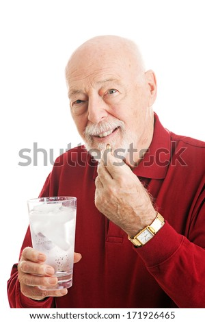Portrait of a healthy senior man taking omega 3 fish oil with a glass of ice water.  White background.   - stock photo