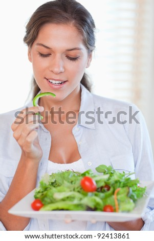 Portrait of a healthy woman eating a salad in her kitchen - stock photo