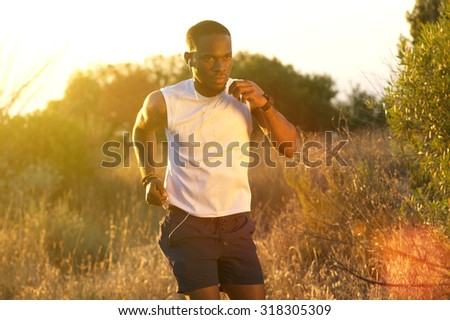 Portrait of a healthy young african american man running outside - stock photo