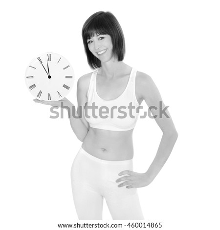 Portrait of a healthy young woman holding a clock showing five minutes to twelve, isolated on white studio background, monochrome photo - stock photo