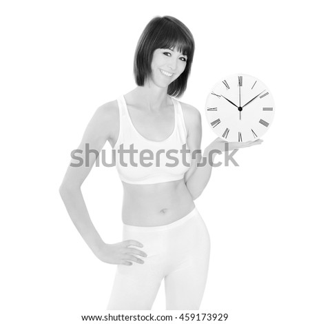 Portrait of a healthy young woman holding a watch, isolated on white studio background, monochrome photo - stock photo