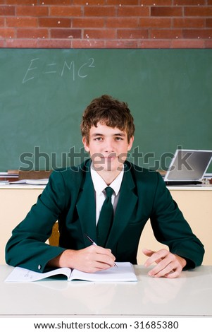 Portrait of a high school boy smiling with book on table in classroom