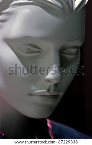 Portrait of a highly detailed human mannequin in three quarter view looking down.