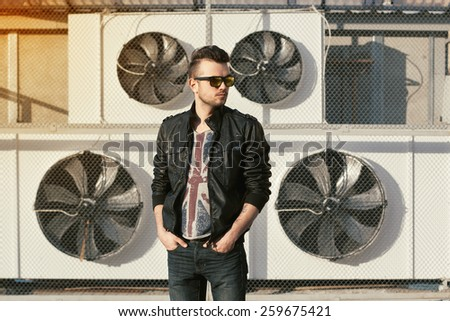 Portrait of a hipster in a black leather jacket and sunglasses. Stands near air conditioners. - stock photo