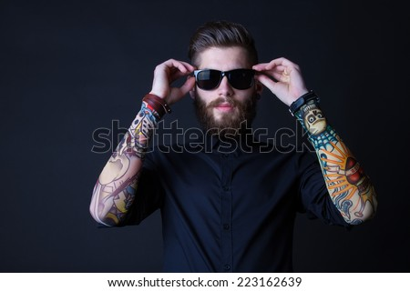 portrait of a hipster man wearing colourful tattooes on his arms posing over a  black background - stock photo