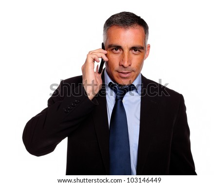 Portrait of a hispanic professional businessman conversing with a mobile looking to you against white background - stock photo