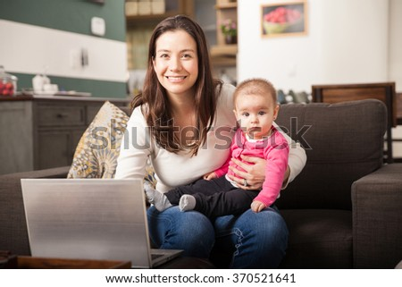 Portrait of a Hispanic young mother looking after her baby daughter and working on a laptop computer at home - stock photo