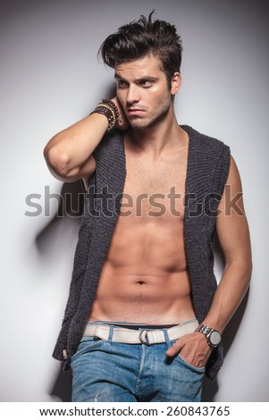 Portrait of a hot fashion man looking away while leaning on a wall with one hand in his pocket. - stock photo