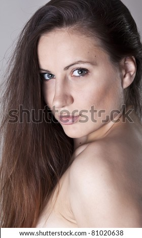 Portrait of a hot young woman looking confidently against grey background - stock photo
