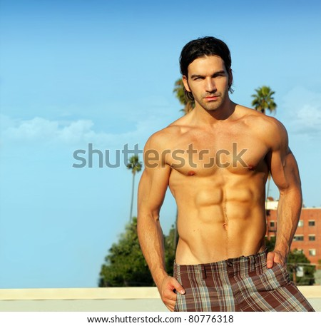 Portrait of a hunky shirtless male model outdoors - stock photo