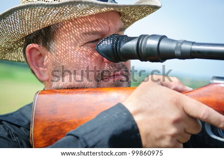 portrait of a hunter with a rifle and scope. outdoors. man aims. close-up. curly falls the shadow of the hat. face with stubble - stock photo