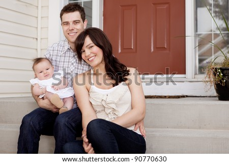 Portrait of a husband and wife with small baby child - stock photo