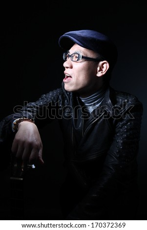 Portrait of a Japanese man with guitar/Japanese musician/A low key portrait of a middle aged Japanese man playing guitar with a cap and leather jacket posing dramatically