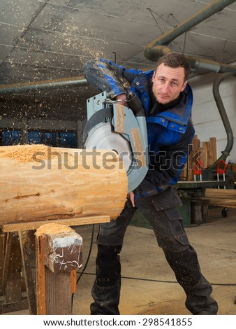 Portrait of a joiner cutting trunk with a chainsaw in his workshop - stock photo