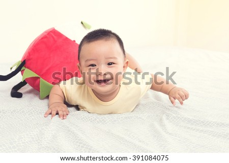 Portrait of a jovial baby on the bed in his room - stock photo