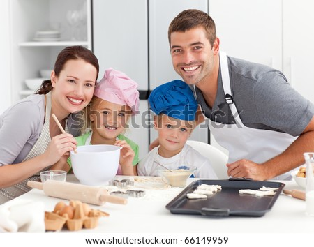 Portrait of a joyful family cooking little cakes in the kitchen