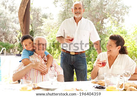 Portrait of a joyful family gathering around a healthy lunch food eating table outdoors during a summer holiday in a vacation garden home. Fun, love and affection family enjoying the sun, lifestyle. - stock photo