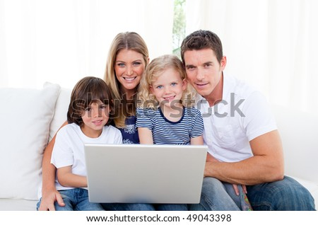 Portrait of a joyful family using a laptop sitting on sofa at home - stock photo