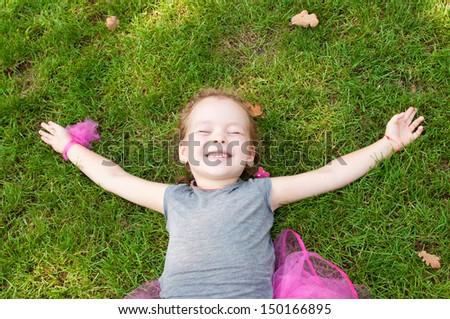 Portrait of a joyful little girl lying on grass - stock photo