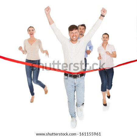 Portrait Of A Joyful Man With Hand Raised Crossing The Winning Line