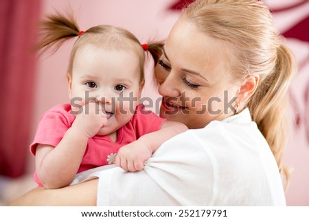 Portrait of a joyful mother and her baby daughter at home - stock photo