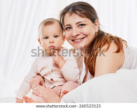 Portrait of a joyful mother and her baby daughter in the bed