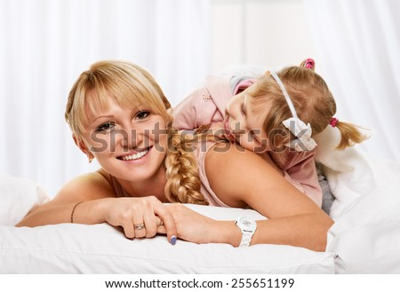 Portrait of a joyful mother and her daughter in the bed