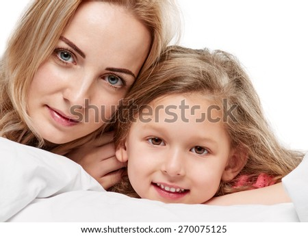 Portrait of a joyful mother and her daughter in the bed on white - stock photo