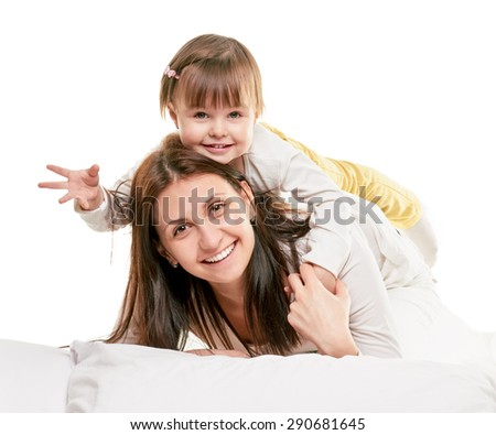 Portrait of a joyful mother and her daughter in the bed on white background - stock photo