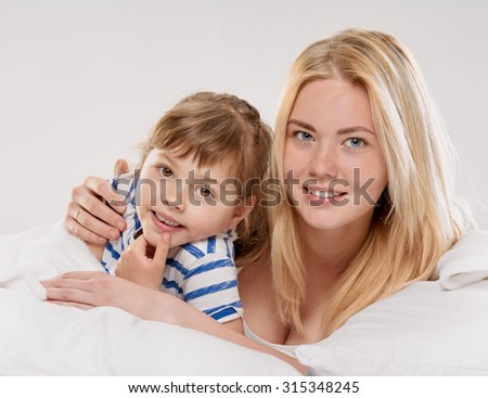 Portrait of a joyful mother and her little daughter in the bed on light grey background