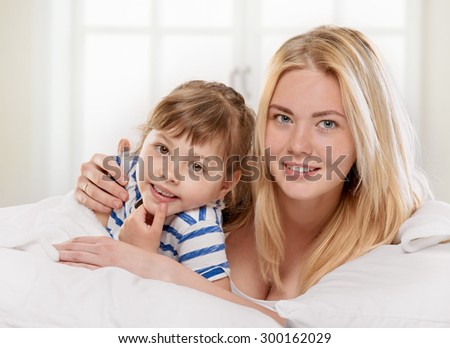 Portrait of a joyful mother and her little daughter in the bed on light window background
