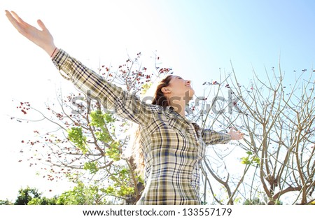Portrait of a joyful young woman being playful with her arms outstretched and enjoying the sun during a spring day against a sunny sky in a park. - stock photo