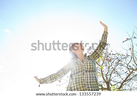 Portrait of a joyful young woman being playful with her arms outstretched with the sun rays filtering through her hair, smiling. - stock photo