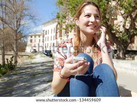 Portrait of a joyful young woman listening to music with her smartphone in the city during a sunny day.